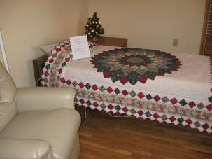 A resident room, with pretty quilt on the bed and comfortable chair at its side